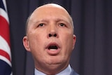 Mr Dutton is standing in front of two Australian flags and a blue curtain, mid sentence. He's standing behind a lectern.