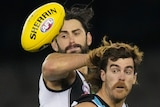 A Collingwood AFL player competes for the ball with a Port Adelaide opponent.