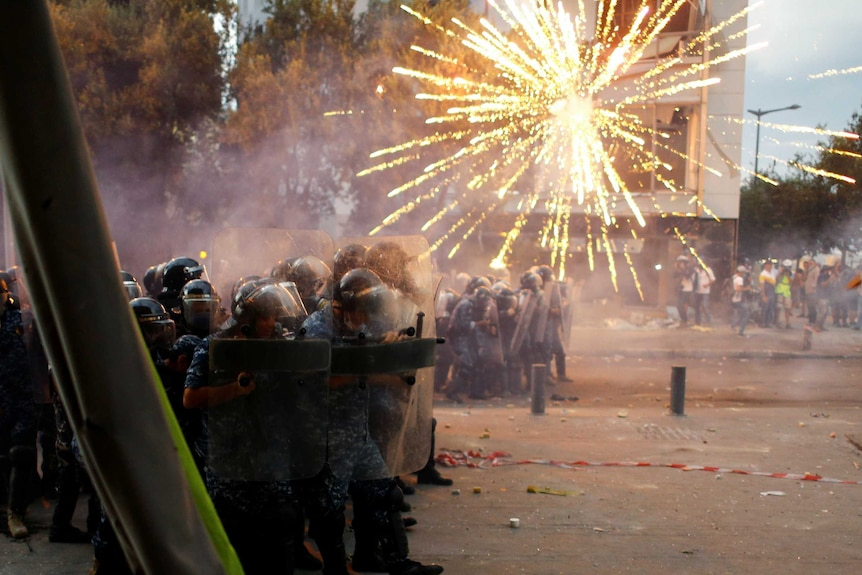 A firework explodes as police in riot gear stand in a street