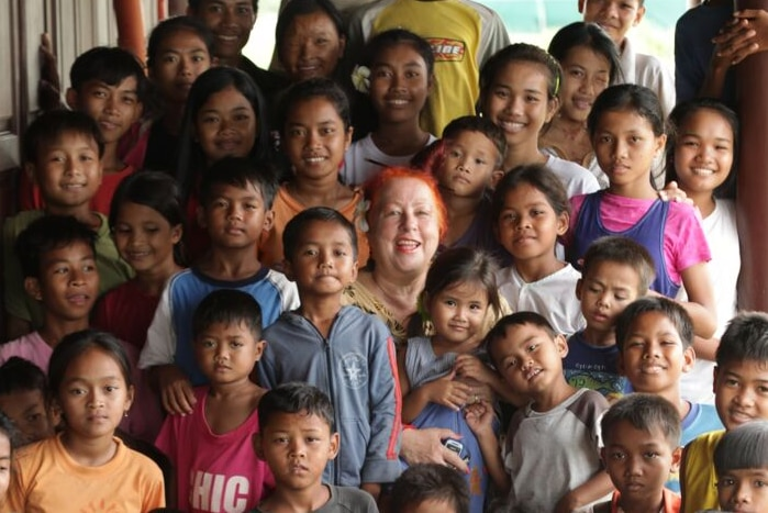 Geraldine Cox surrounded by children at an orphanage