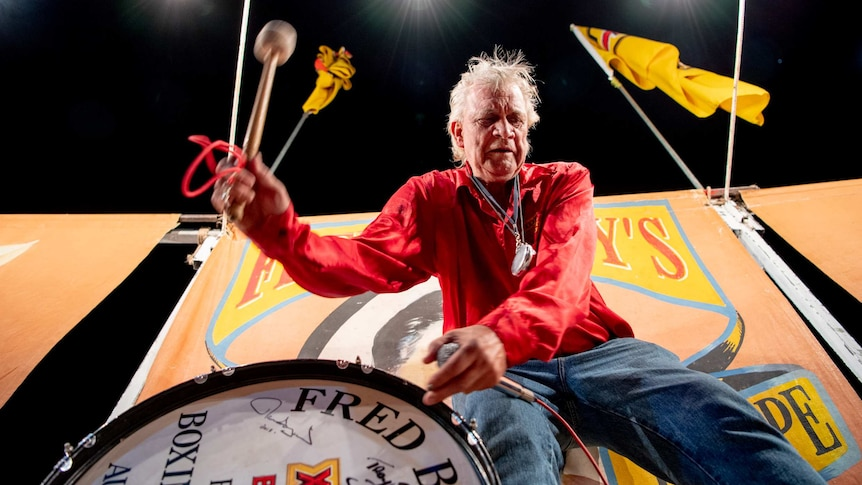 Fred Brophy, in a red shirt, bangs on a drum outside an orange tent.