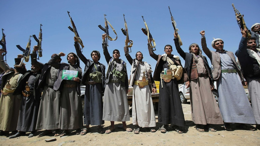 A line of tribesmen hold their weapons straight in the air as they chant slogans.