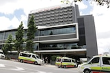 Ambulances lined up in the street and under the Hotel Grand Chancellor building at Spring Hill in Brisbane