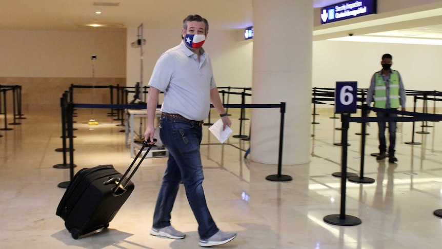 US Senator Ted Cruz, wearing a Texas flag face mask, carrying luggage through an airport.