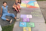 Children smile next to chalk drawings on a footpath.