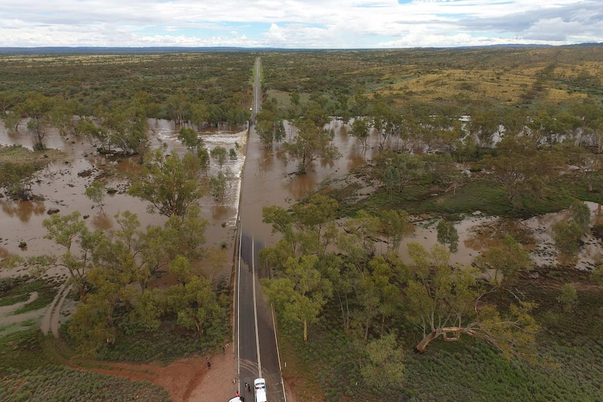 A flooded roadway in remote Northern Territory, cutting off communities from supplies.