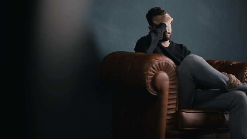 A man sits on a sofa holding his head in his hands.