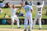 A red-faced Test bowler roars and raises his arms after taking a wicket.