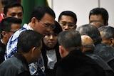 Jakarta's Christian governor Basuki Tjahaja Purnama (L), popularly known as Ahok, speaks to a ring of lawyers surrounding him.