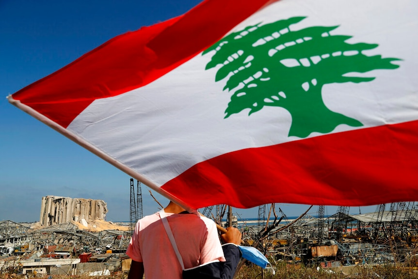 A man holds the Lebanese flag, as he looks at the scene of Tuesday's explosion that hit the seaport of Beirut.