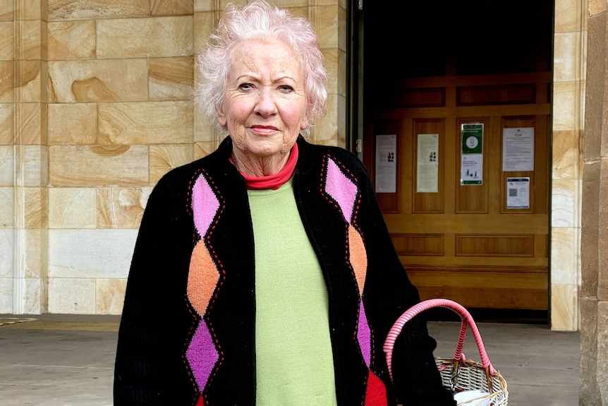 A woman holding a bag outside court.
