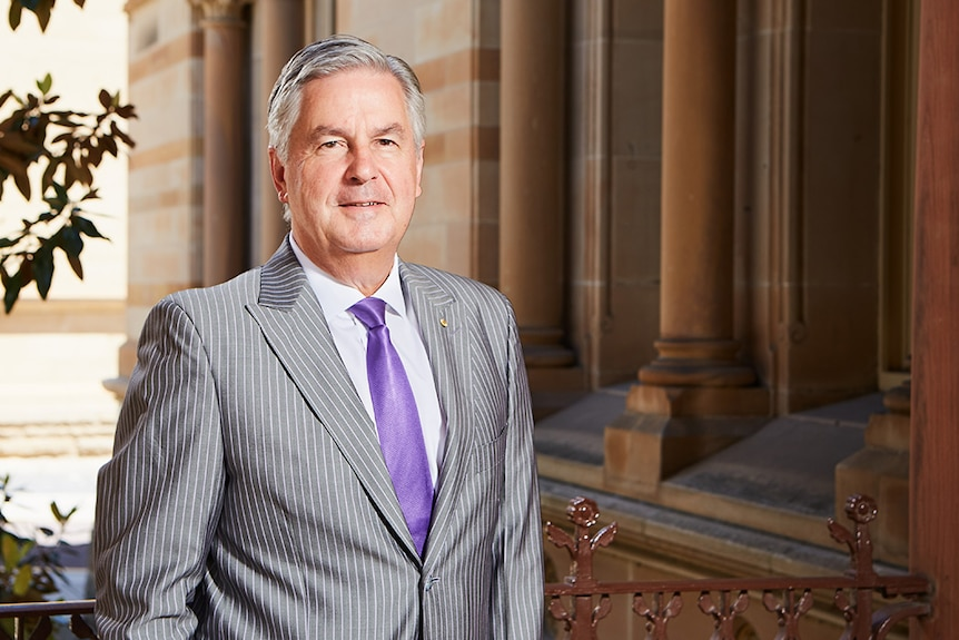 A man with grey hair and a suit, with a purple tie, stands in front of a building with sandstone columns.