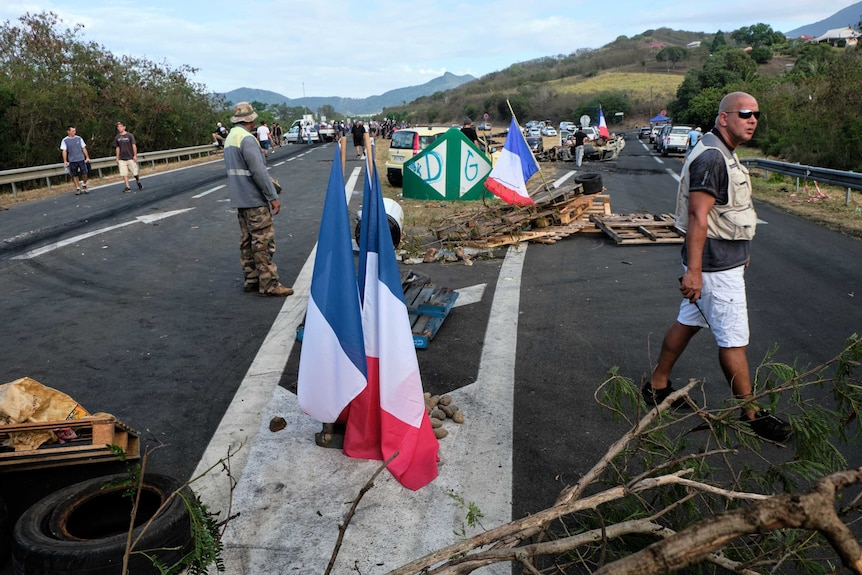 Men stand beside debris piled on the road, with French flags waving.