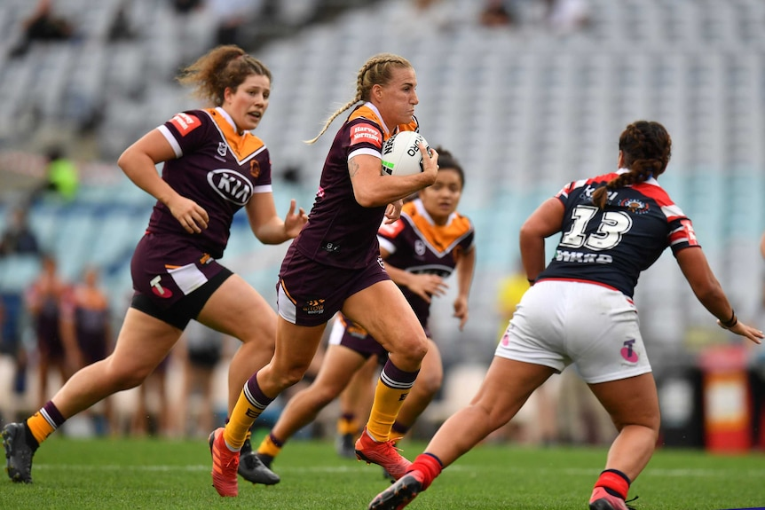 A player tucks the ball under her arm as she runs toward the tryline in an NRLW game.