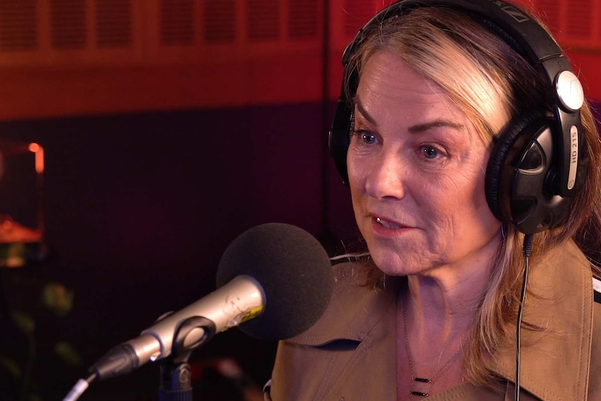 A woman with blonde hair and a beige jacket wearing headphones and speaking into a microphone.