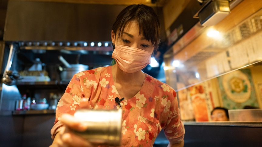 A young Japanese woman in a face mask seasoning meat with a salt shaker