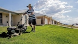 A man mowing the lawn outside a row of new houses