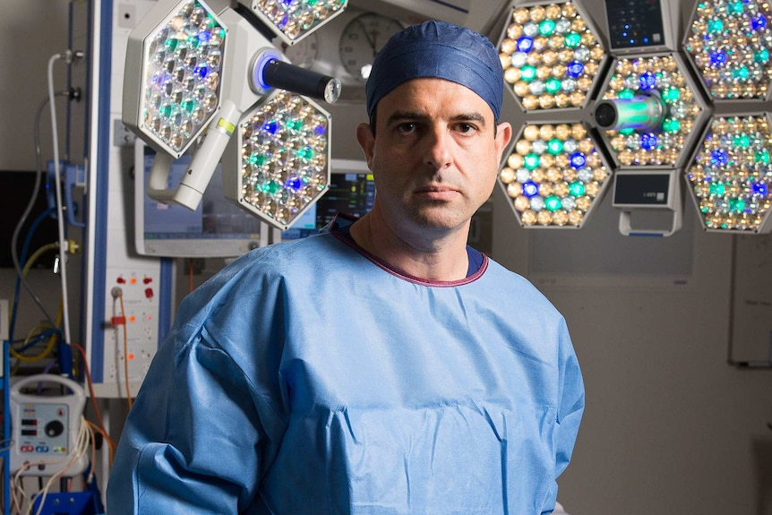 A mid-shot of AMA president Omar Khorshid standing in an operating theatre with scrubs on and holding a face visor.