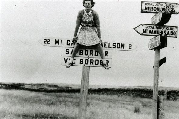 A black and white photo of a woman sitting on the marker for the SA/Victoria border.