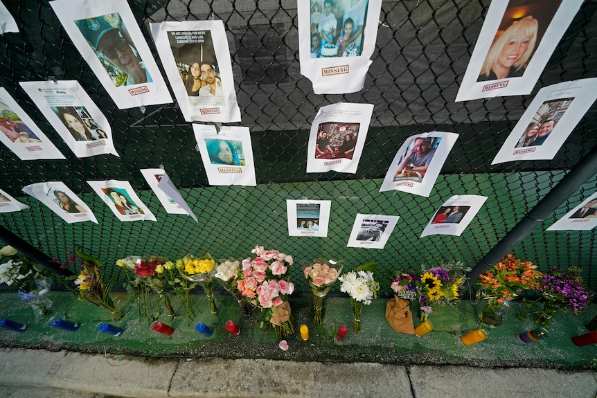A makeshift memorial bears photos of some of the missing people that hangs from a fence.