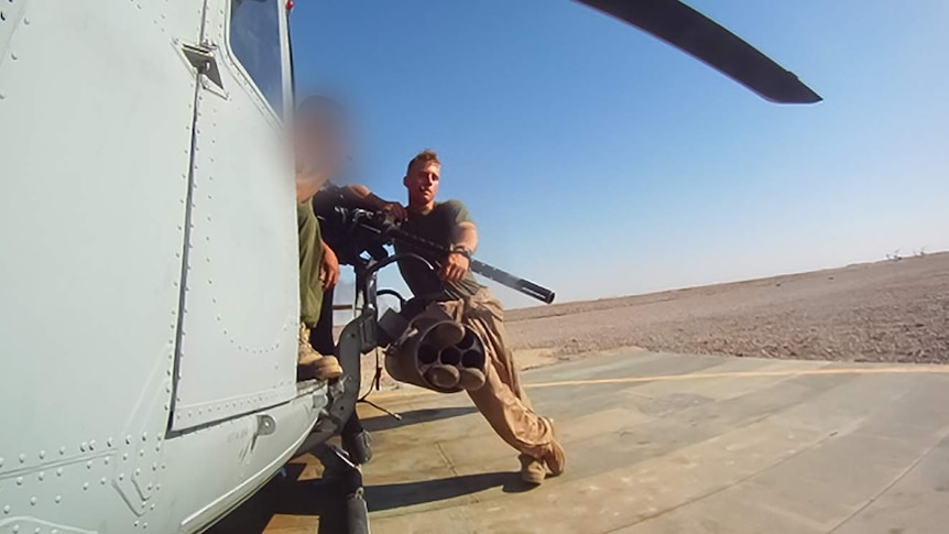 A man in uniform leans up against a helicopter.