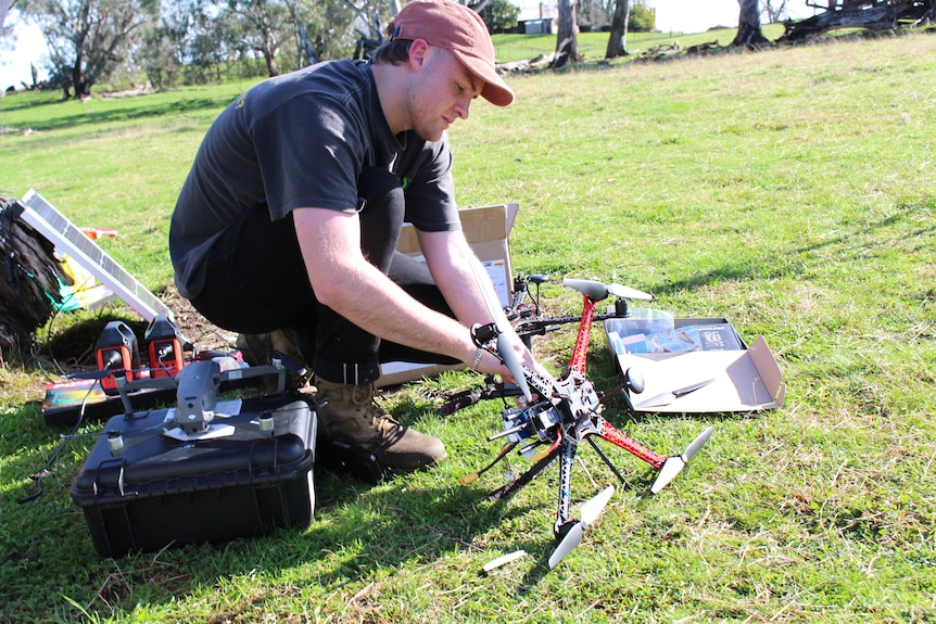 Man wearing cap and kneeling, inspecting a red and black drone
