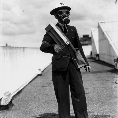 Man in gas mask and helmet holding equipment