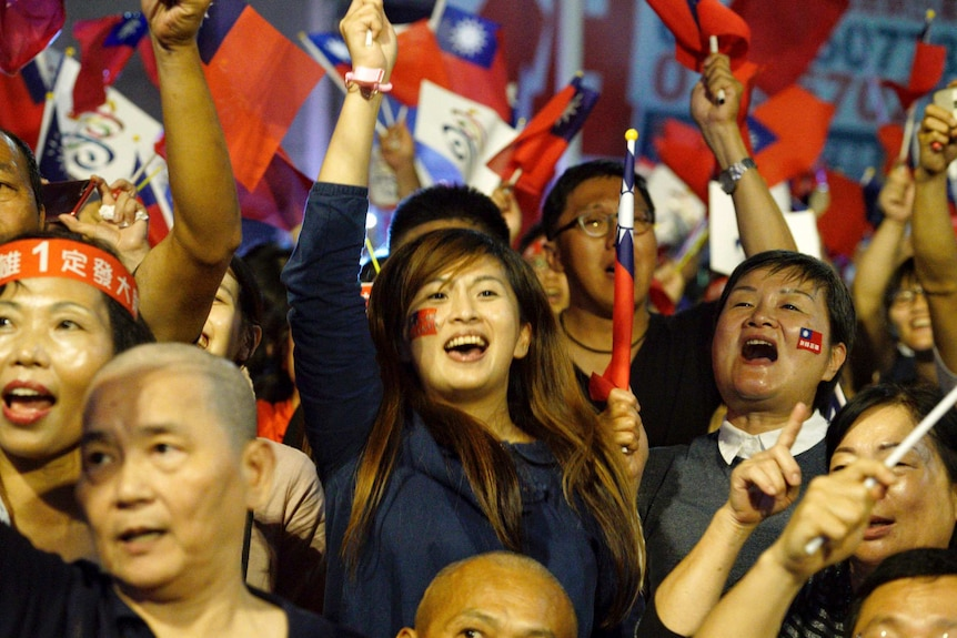 Crowd of Kuomintang supporters wave Taiwanese flags with miniature flags stuck onto supporters' cheeks.
