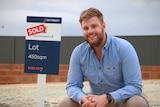 A man wearing a blue work shirt at an empty block of land