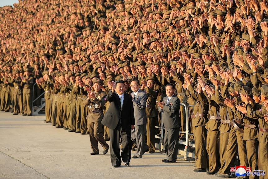 Kim Jong Un wearing a western-style suit walks past a crowd of applauding soldiers