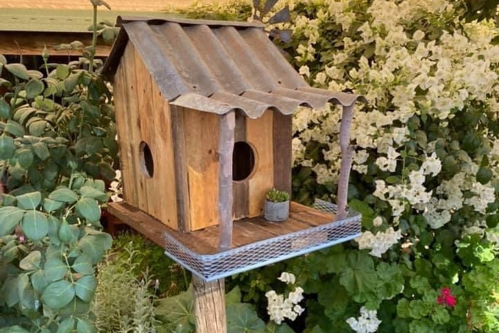 Rustic birdhouse made from old timber and tin with a cottage garden in background.