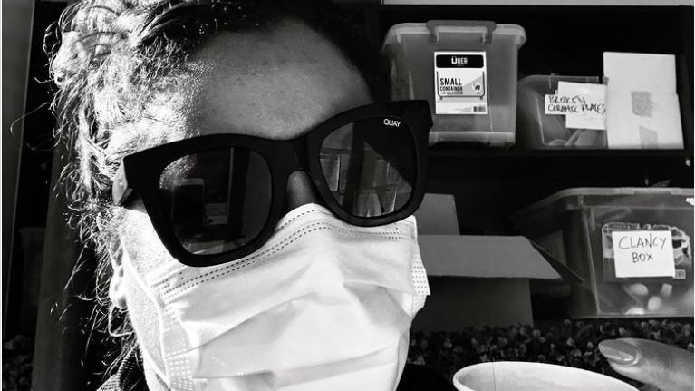 Shareena Clanton wears a face mask in a black-and-white photo of her underneath a 'Ramsay St' sign.