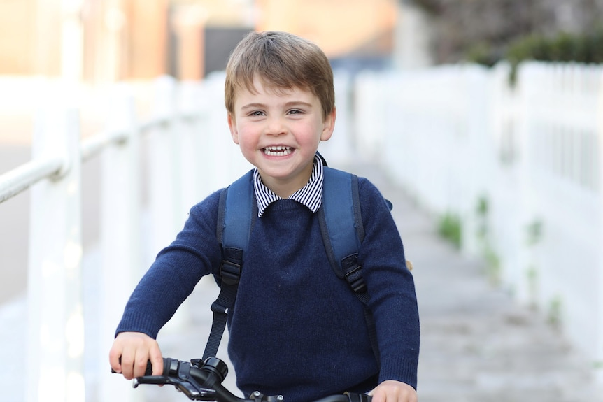 Britain's Prince Louis smiles on a red bicycle in a photo taken by his mother before his first day of school.