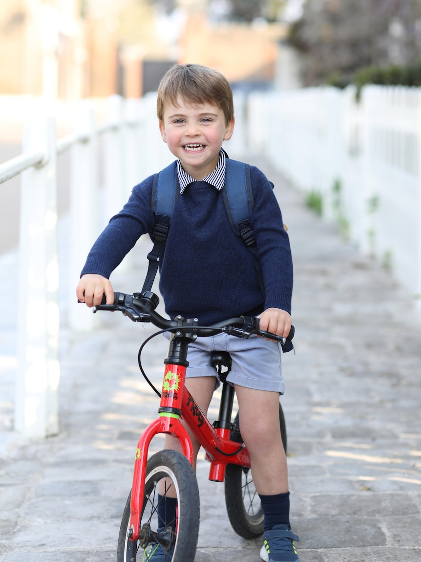 Britain's Prince Louis smiles on a red bicycle