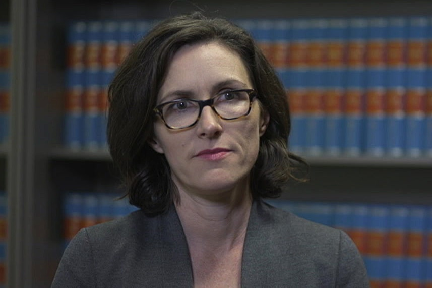 A woman wearing a grey blazer and tortoise-shell spectacles looks to the right of the camera.