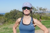 A woman in running gear standing on a headland looks at the camera.