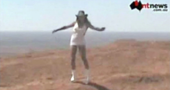 Woman in a white dress and akubra stands on top of Uluru