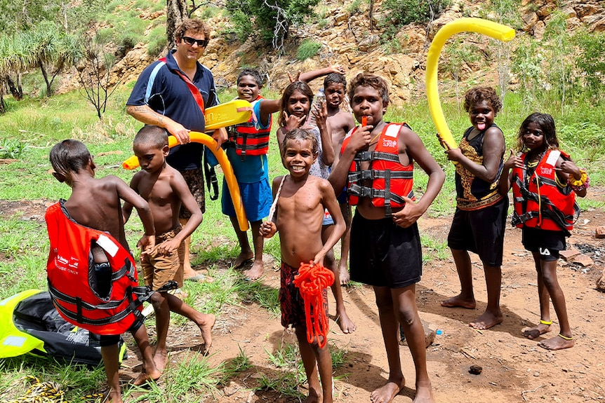 A group of children wearing life jackets stands by a river near Warmun.