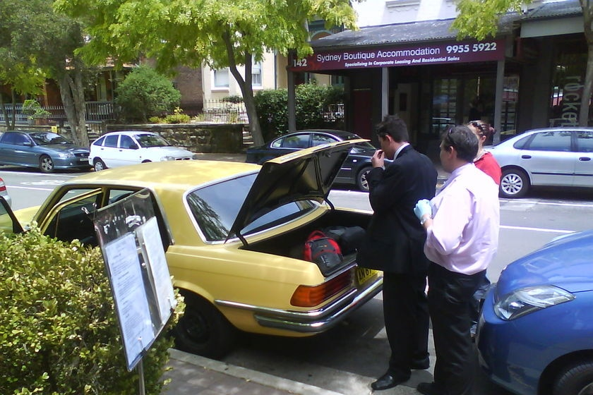 Detectives search a car after arresting two men at a McMahon's Point cafe.