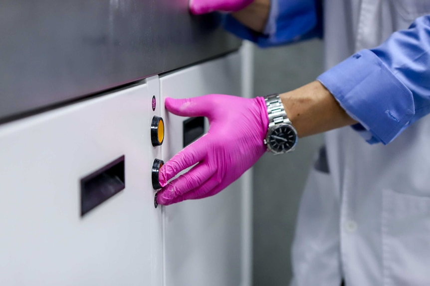A pink-latex gloved-hand pushes a red button on a white and silver 3D printing machine