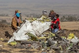 Men wearing masks and headwear lift up wreckage of an aircraft in Ethiopia.