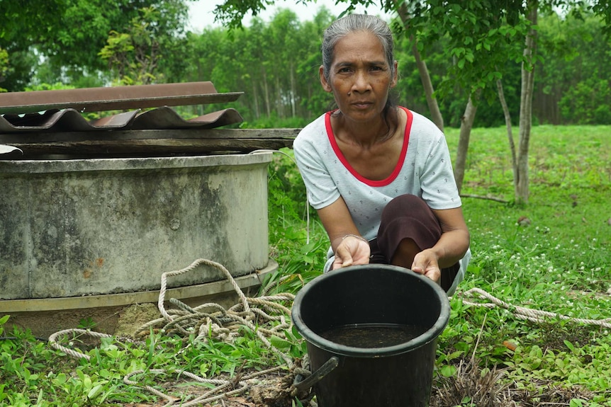 A woman crouching next to a well, tipping a bucket of brown water