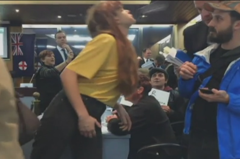 A woman appears to towards a man in a crowded area.