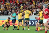 Wallabies players look dejected as the referee blows his whistle to end a loss to Wales.