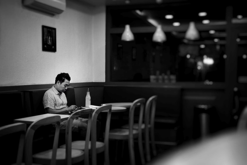 A man sits alone in a cafe. He's looking at his phone