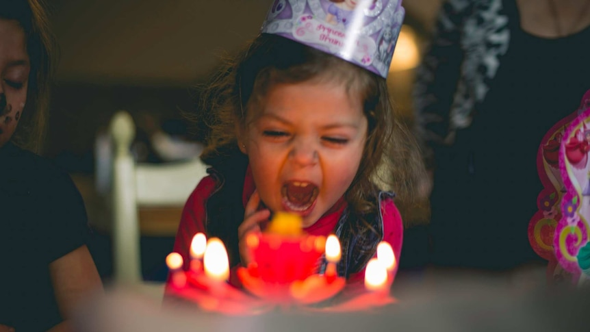 Girl with party hat and cake blowing out candles on a cake for a story about surviving birthday parties