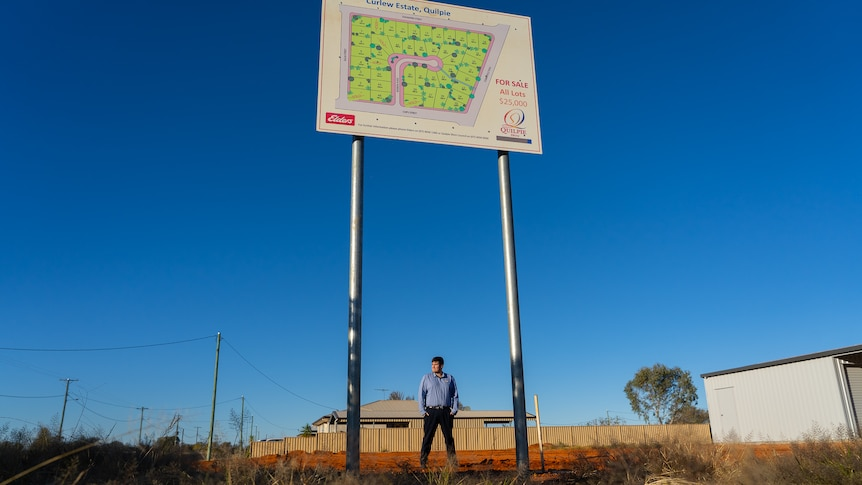 A man stands on a vacant housing block underneath a sign advertising land for sale.