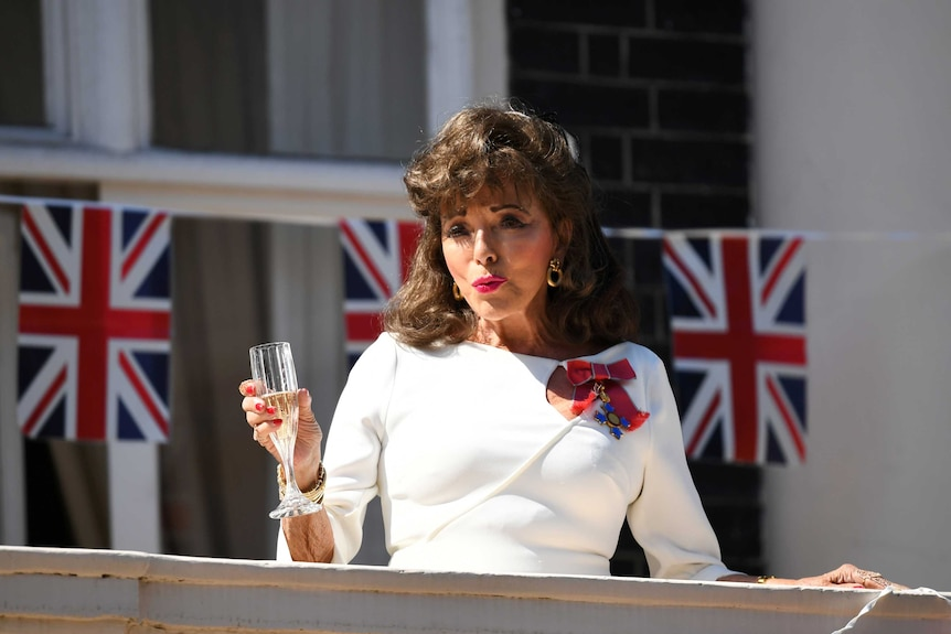 A woman drinks a glass of champagne with Union Jack flags in the background