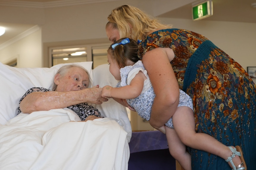 A woman holds her toddler daughter while she interacts with an aged care resident.