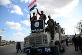Shiite fighters celebrate on a truck seized from Islamic State militants in Tikrit
